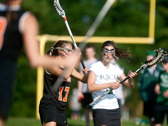 Rice's Michelle Bolger maintains possession against Middlebury's Keagan Dunbar during the final moments of the teams' Division I girls lacrosse quarterfinal on Saturday.