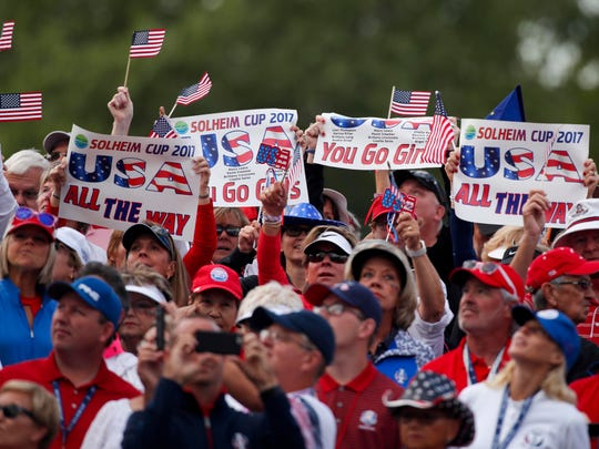 USA fans hold up signs on the first hole during the first round morning session during The Solheim Cup international golf tournament at Des Moines Golf and Country Club.