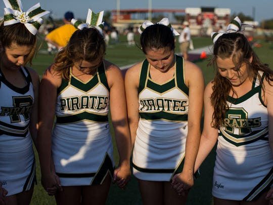 Rockport-Fulton cheerleaders huddle before the schools football game against Sinton at Pirates Stadium in Sinton on Friday, Sept. 8, 2017.