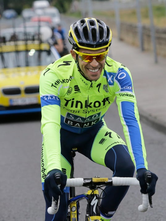 Spain's Alberto Contador smiles when talking to his teammates during a training ride ahead of the Tour de France cycling race in Leeds, Britain, Thursday, July 3, 2014. The Tour de France will start on Saturday July 5 in Leeds, and finishes in Paris on Sunday July 27. (AP Photo/Laurent Cipriani)