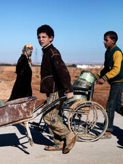 A Syrian refugee boy uses a wheelchair in December