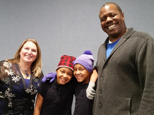 Jeff Beard, director of the Salvation Army's Community Center (right), and Tara Houser, vice president of marketing for First Capital FCU (left), pose for a picture with twin girls who are trying out their new hats and gloves.