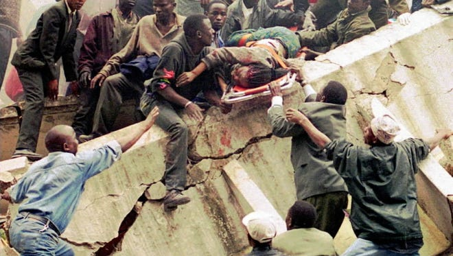 FILE--Rescue workers carry a woman, rescued from the U.S. Embassy, over the rubble of a collapsed building next to the embassy in Nairobi, Kenya, following a bombing in this Aug. 7, 1998, file photo. Four followers of Osama bin Laden were convicted Tuesday, May 29, 2001, of charges in the nearly simultaneous bombings of two U.S. embassies in Africa that killed 224 people and buried thousands of others under piles of tangled metal and concrete.