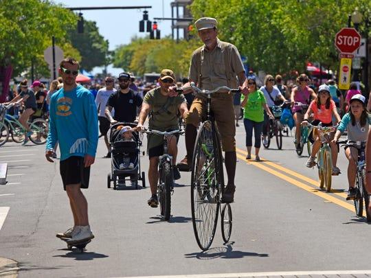 Bike riders make their way up Palafox Pl. Saturday,