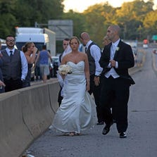 Newlyweds Robert and Katherine Mitariten walk down the median on I-287 in Port Chester Sept. 12, 2014. The couple had been stuck in traffic for over an hour, following an accident while in route to their wedding reception at Fountainhead in New Rochelle.
