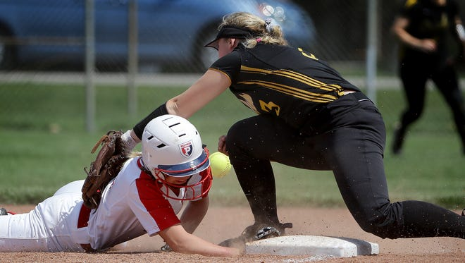 Plainfield's Mackenzie Dalton,left, slides safely back into the first base as Avon's Nicole Large,right, misses the ball during the championship game in the Hendricks County girls softball tournament Saturday, April 15, 2017, afternoon at Brownsburg High School. The Avon Orioles defeated the Plainfield Quackers 11-1.