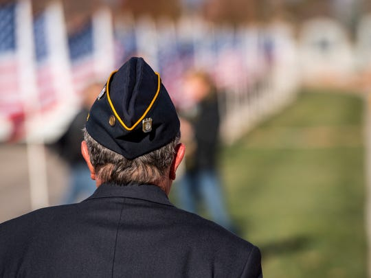 A United States military veteran walks along a path lined with flags at Veteran's Park in Cedar City on Monday, November 12, 2018.