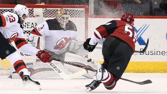 New Jersey Devils goalie Keith Kinkaid (1) positions himself for a save on the shot by Arizona Coyotes' Jason Demers (55) as Stefan Noesen (23) defends during the first period of an NHL hockey game, Saturday, Dec. 2, 2017, in Glendale, Ariz.