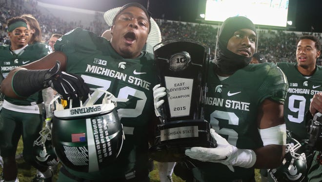 Michigan State Spartans Craig Evans and Aaron Burbridge celebrate with the East Division Championship trophy after beating the Penn State Nittany Lions 55-16 on Saturday , November 28, at Spartan Stadium in East Lansing Michigan.