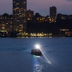 A police boat is seen on the scene of a plane crash in the Hudson River in New York on May 27, 2016. According to media reports, the plane that crashed is likely a P-47 World War II-era aircraft.