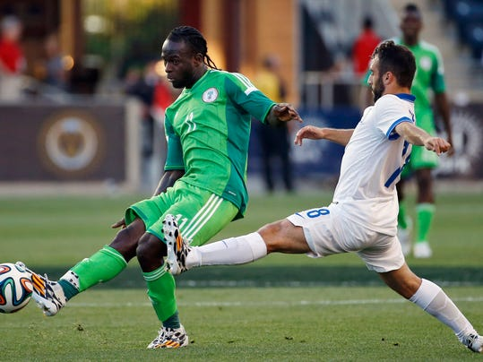 Nigeria forward Victor Moses, left, kicks the ball away from Greece midfielder Ioannis Fetfatzidis during the first half of an an international friendly soccer match, Tuesday, June 3, 2014, in Chester, Pa. (AP Photo/Matt Slocum)