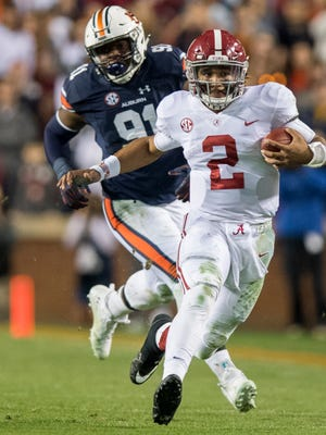 Alabama quarterback Jalen Hurts (2) is chased by Auburn defensive lineman Nick Coe (91) in the Iron Bowl in Auburn, Ala. on Saturday November 25, 2017. (Mickey Welsh / Montgomery Advertiser)