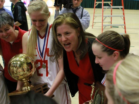 Coach Ute Otley for CVU embraces her team as they celebrate their state title win over Rice back in March.
