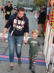 Detroit Medical Center staff member Summer Sumner of Sterling Heights escorts 4-year-old Benjamin Tanghe of Center Line out of harms way after he ran onto the course near the finish line of the Detroit Free Press/Chemical Bank Marathon on Sunday, Oct. 15, 2017.