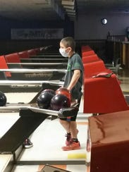 Bowling alone during off-hours, wearing a mask to prevent
