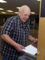 David Wojtowicz from Farmington Hills stuffs his ballot in box.