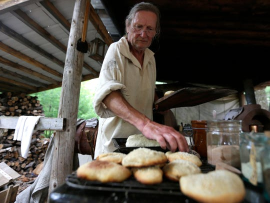 A man lays out fresh bread baked from the classic clay