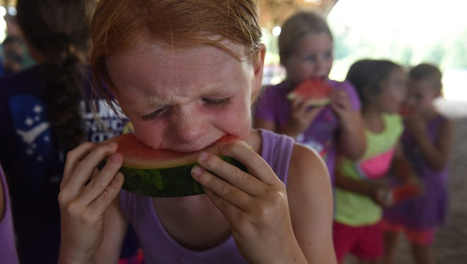 Ashley Romanowski, 8, of Salisbury eats a slice of watermelon during the 4-H Olympics at the 2016 Somerset County Fair.