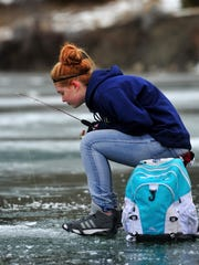 Riley Gorder, a seventh-grader at East Middle School, watches her line during the Hooked on Fishing Not Drugs Club's ice fishing trip at Holter Lake. Fish caught that were caught are headed for dissection, not the frying plan.