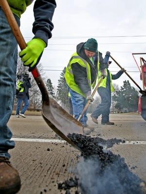 Adam White, center, and others with the Department of Public Works repair potholes on South Keystone Avenue in an IndyStar file photo.