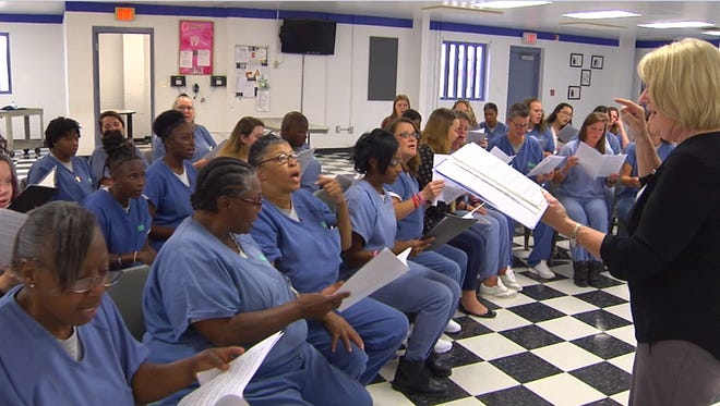 Video screenshot of Florida State University professor Judy Bowers conducting a choir of FSU students and inmates at Gadsden Correctional Facility in Quincy.