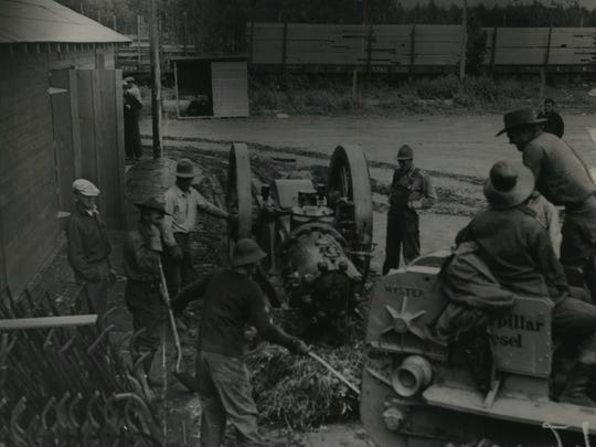 Colonist in Alaska's Matanuska Valley work to unload an engine that will generate electricity for the settlement's community center. This photo was published in the July 21, 1935, Milwaukee Journal.