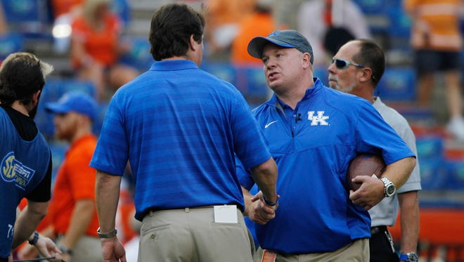 Sep 13, 2014; Gainesville, FL, USA; Kentucky Wildcats head coach Mark Stoops and Florida Gators head coach Will Muschamp talk prior to the game at Ben Hill Griffin Stadium. Mandatory Credit: Kim Klement-USA TODAY Sports