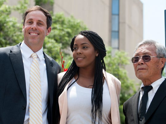 Valanica Fletcher received a scholarship from local businessman Hea-Bok Chang, right, and Chris Dickert, left, during the unveiling of the Korean War monument he donated in Montgomery, Ala., on Friday May 27, 2016.