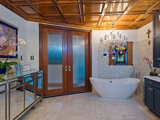 A crystal chandelier illuminates the master bath soaking tub surrounded by a unique glass tile corner wall under a wood paneled ceiling.