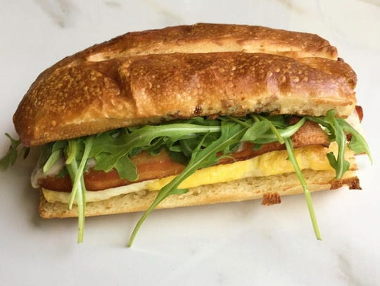 A breakfast sandwich from Marie's Sandwich Bar, created by chef/owner Nick Capaldi, includes eggs, applewood smoked bacon, aged cheddar and arugula on a pretzel roll.