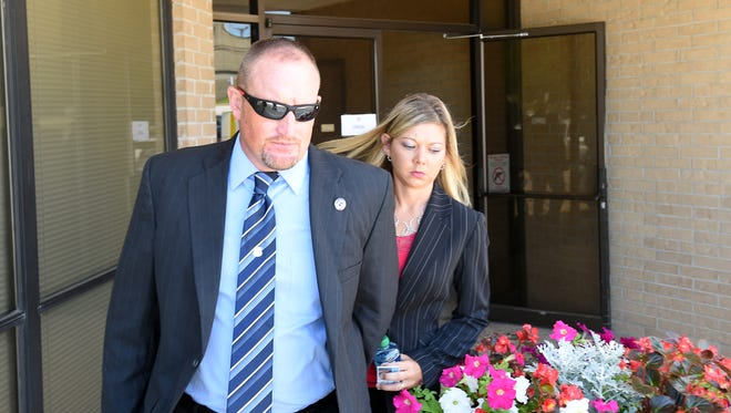 Bull Shoals Police Chief Daniel Sutterfield and his wife, Andrea, leave the federal court building in Harrison on Tuesday.