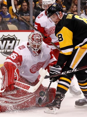 Penguins' Brian Dumoulin can't get his stick on a rebound in front of Red Wings goaltender Jimmy Howard in the second period in Pittsburgh, Saturday.