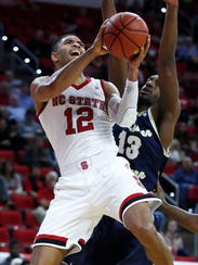 North Carolina State's Torin Dorn (2) drives around Charleston Southern's Jamal Thomas (15) during the first half of an NCAA basketball game at PNC Arena in Raleigh, N.C. Sunday, Nov. 12, 2017. (Ethan Hyman/The News & Observer via AP)