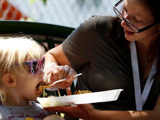 Rose Garber, right, feeds her daughter Priscilla Garber,