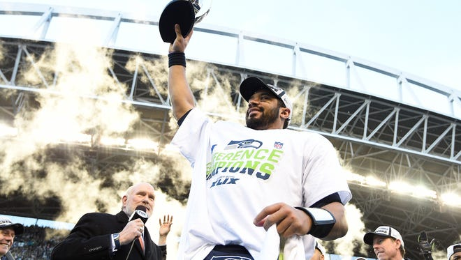 Seattle Seahawks quarterback Russell Wilson (3) holds the George Halas trophy following his team's 28-22 victory against the Green Bay Packers in the NFC Championship game at CenturyLink Field in Seattle on Jan. 18, 2015.