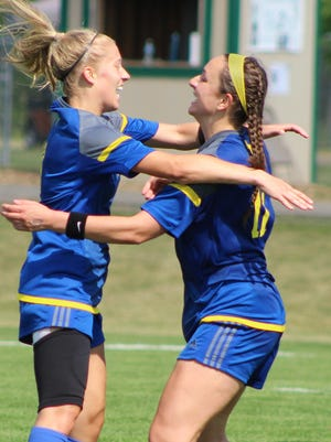 Marian junior Jansen Eichenlaub (left) celebrates with teammate Annie Bruce who had just scored what proved the game-winning goal just seconds before halftime Saturday in the D-2 state championship game against Forest Hills Northern.