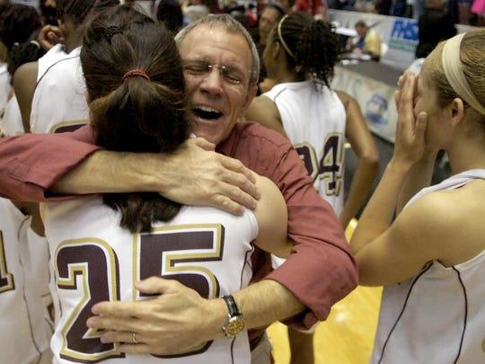 Astronaut head basketball coach Gregg Hostetler hugs Pam Walker as they and teammate Lauren Jenkins (right) celebrate the War Eagles Class 4A championship in 2009.