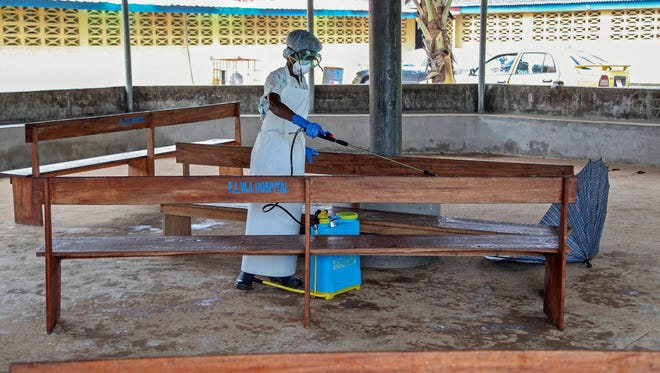 A nurse from Liberia sprays disinfectant in the waiting area for visitors at the ELWA Hospital in Monrovia where U.S. doctor Kent Brantly is being quarantined in the hospital's isolation unit after contracting the Ebola virus.