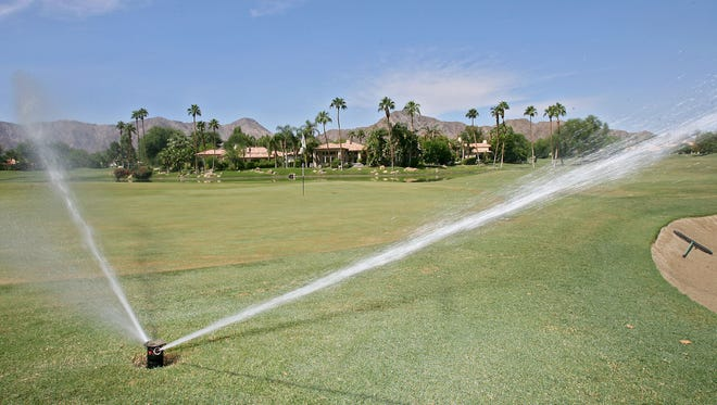 A pop-up sprinkler waters the 9th green area at the Jerry Pate course at Rancho La Quinta Country Club.
