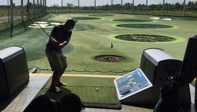 Casey Moore takes a swing at Topgolf in Ashburn, Va.