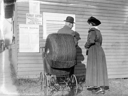 A man talks to a woman outside a polling place in this circa 1918 photo; the wooden polling booth has posters to instruct the voter.