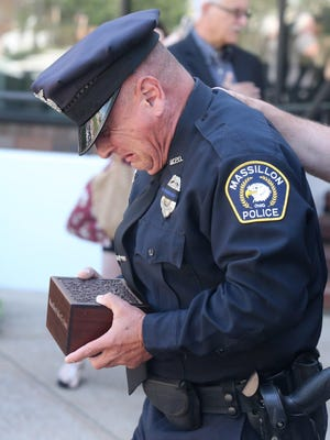 Massillon police officer Miguel Riccio reacts while carrying the ashes of his K-9 Inca during a rememberance for the police dog at Duncan Plaza in Massillon on Wednesday, June 3, 2020.