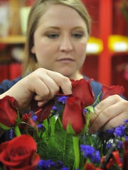Morgan Hrncirick          {cq}         of The Basketcase and Flower Shop puts the finishing touches on an arrangement of roses Monday afternoon. The red rose was the favorite flower of Venus, the Roman goddess of love.
