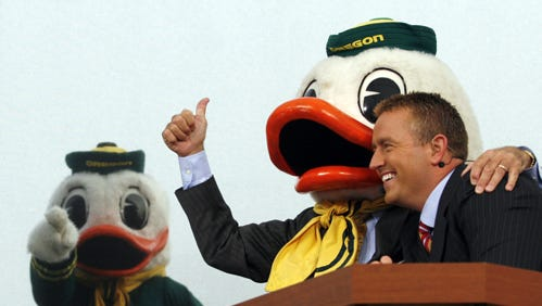College Football Analyst Lee Corso, center, gives College Football Studio Analyst Kirk Herbstreit a hug after  putting on the Duck head gear during The ESPN College GameDay at Alton Baker Park, just across the footbridge from the south end of Autzen Stadium in Eugene Saturday, Nov. 3, 2007. Corso predicted a win for Oregon in the Oregon Arizona State game.