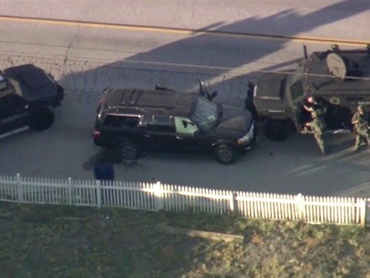 Armored vehicles surround an SUV following a shootout
