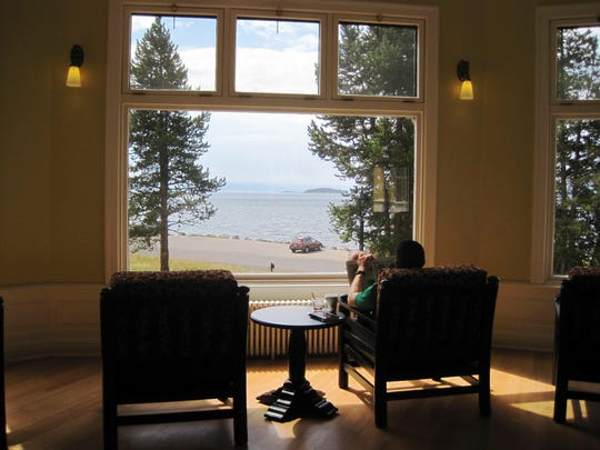 A visitor reads inside Lake Hotel in Yellowstone National Park.