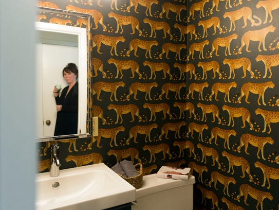The guest bathroom has distinctive wallpaper. Allison
