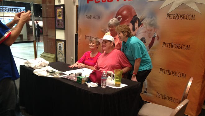 Pete Rose posing for fans for a photo.