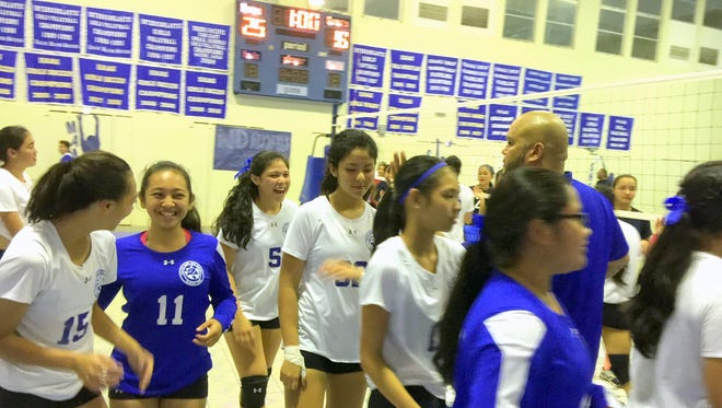 The Notre Dame Royals are all smiles as head coach Mike Rabago hands out high-fives and the final set score shows on the scoreboard. The Royals defeated the Okkodo High School Bulldogs 25-14, 25-18, 25-18 on Tuesday night to advance to the IIAAG finals