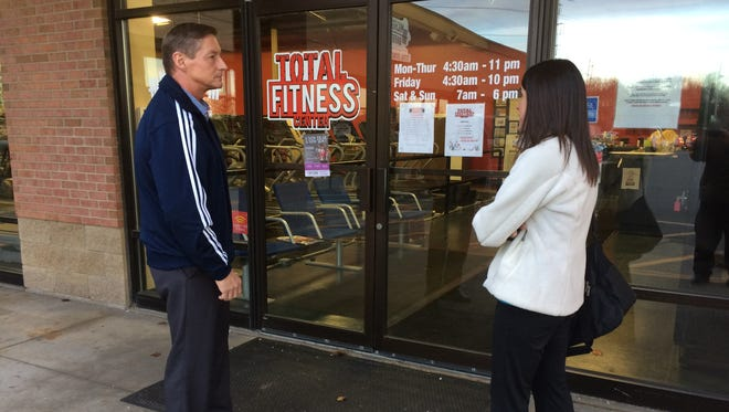 Brighton's Tom Dukes and Howell's Sarah Meyers talk outside the locked Total Fitness Center on Friday.